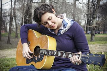 Beautiful young girl playing guitar outdoor