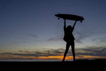 Silhouette of a curly girl with her longboard watching the sunset
