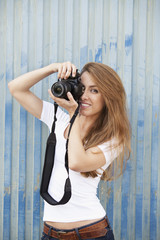 Young woman taking photograph with digital camera, portrait