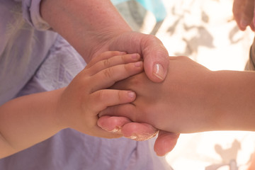 Hands of an elderly woman holding the hand of a baby and a younger woman.