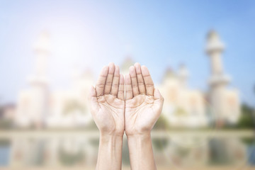 Human hands pray and mosque background.