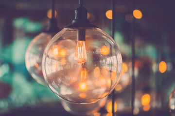 Luxury retro light bulb glowing in vintage filter image.
