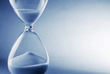 Hourglass clock on light blue background
