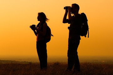 Couple with backpack watching the sunset