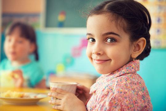 Cute hispanic girl drinking milk at school