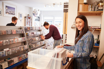 Woman working behind the counter at a record shop