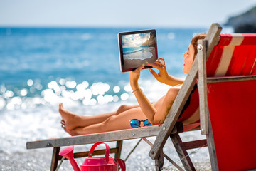 Woman looking photos with tablet on the sunbed