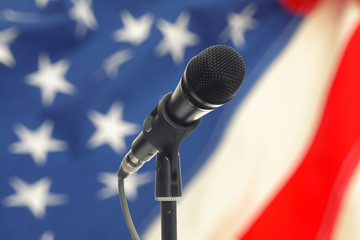 Microphone on stand with USA flag on background