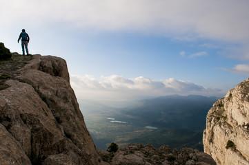 zirve kayalıklardan bölgeyi inceleyen dağcı