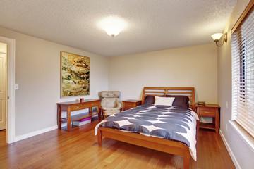 Big bedroom with hardwood floor and window.
