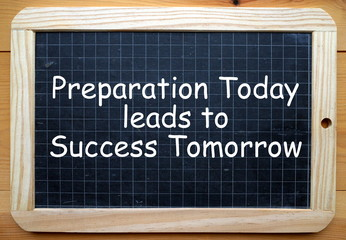 The phrase Preparation Today leads to Success Tomorrow in white text on a slate blackboard
