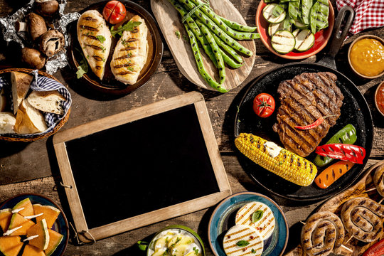 Blank Chalkboard on Wooden Table with Grilled Meal