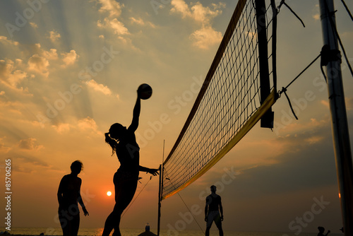 Wall mural Beach volleyball silhouette at sunset , motion blurred