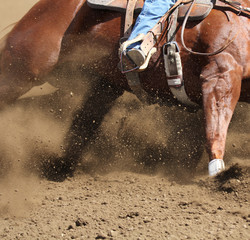 A  close up action photo of a horse sliding around a barrel with dirt flying.