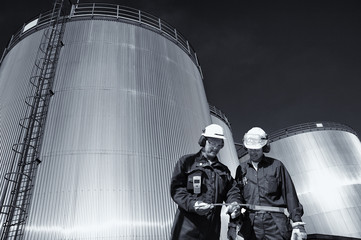 oil workers with large storage tanks, evening shot in blue toning