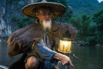 Senior man holding a lamp while traveling by boat