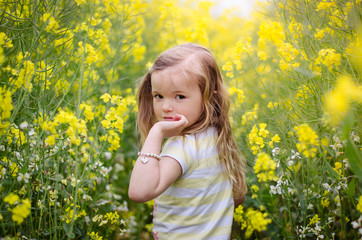 Girl looking over her shoulder in a meadow of yellow flowers
