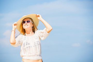 Young skinny caucasian girl at the beach with blue sky on