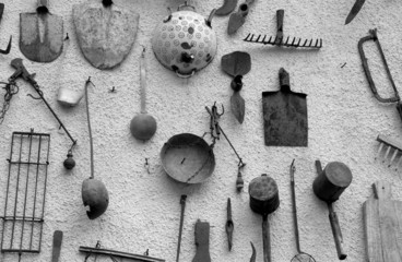 many ancient farming tools hanging on the wall