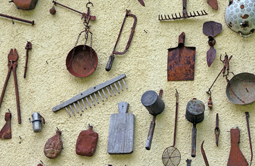 ancient farming tools hanging on the wall of the House