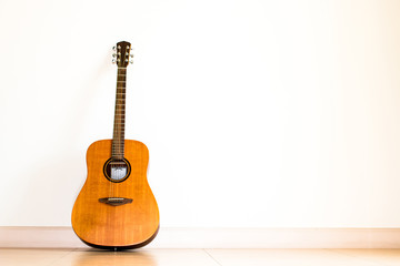 Acoustic guitar standing on floor
