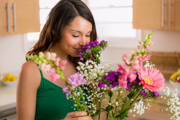 Beautiful woman smelling flowers from her lover at home on valentines day