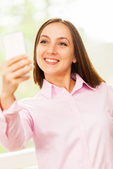 Smiling caucasian woman with pink shirt is doing a selfie with h