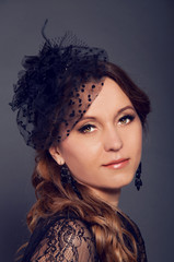 Elegant young woman in black lace dress and veil hat with long c