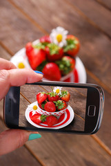 taking photo of fresh strawberries by smartphone