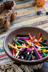 Many colored pencils lying in a clay plate