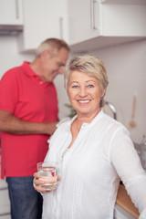 entspannte ältere frau mit einem glas wasser in der küche
