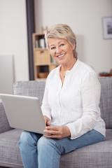 moderne seniorin mit laptop auf dem sofa