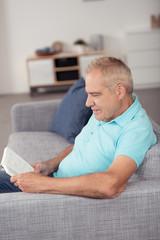 älterer mann sitzt auf dem sofa und liest ein buch