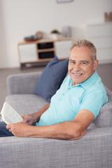 entspannter senior liest ein buch auf dem sofa