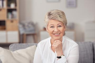 lächelnde seniorin im wohnzimmer auf dem sofa