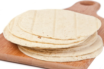 Corn Tortillas – A stack of corn tortillas on a wooden cutting board.