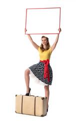 Frau im Rockabilly Kleid steht auf einem Koffer und hält ein Werbeschild