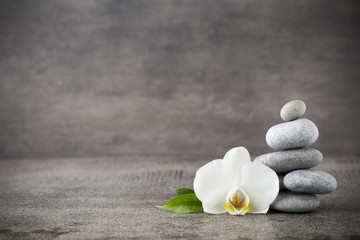 White orchid and spa stones on the grey background.