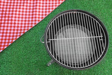 Red Picnic Tablecloth And BBQ Grill Appliance On The Lawn