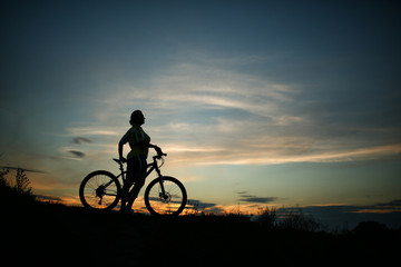 Silhouette of tourist and bike on sky background.
