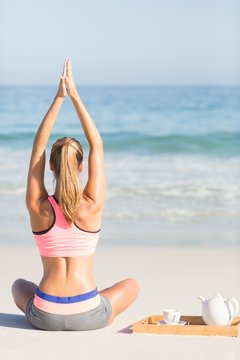 Fit woman doing yoga beside the sea