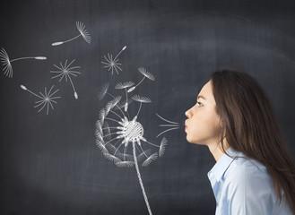 Young woman blowing dandelion on blackboard