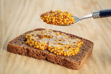 Rye bread slice witth spoon of wholegrain mustard