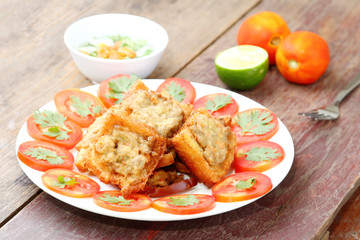 Fried bread with minced pork spread on wood table.