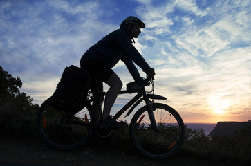 Silhouette of a cyclist on the background of the cloudy sky at s