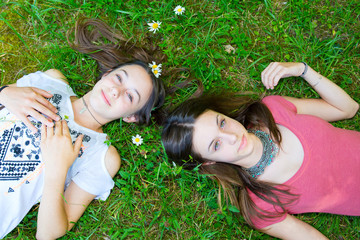 Relaxed young persons (teenage girls) lying in grass and flowers with stretched hand - closed eyes
