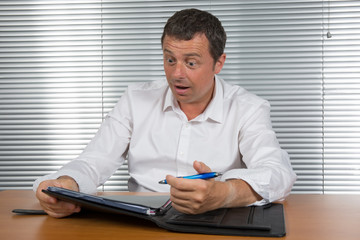 Man at his desk happy to find an idea