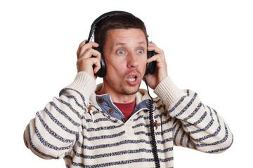 Mann ist entsetzt über das was er mit Kopfhörer hört