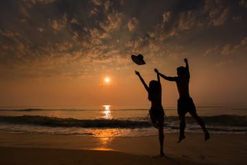 Couple jump and feel happy. On the beach