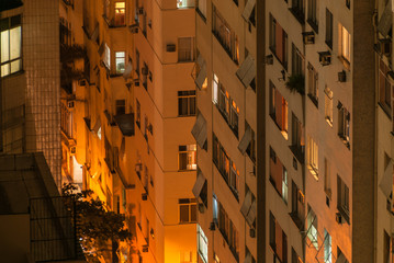 Aerial view architectural facade of residential buildings in Rio de Janeiro. Illuminated apartment windows at night condo buildings closeup for background